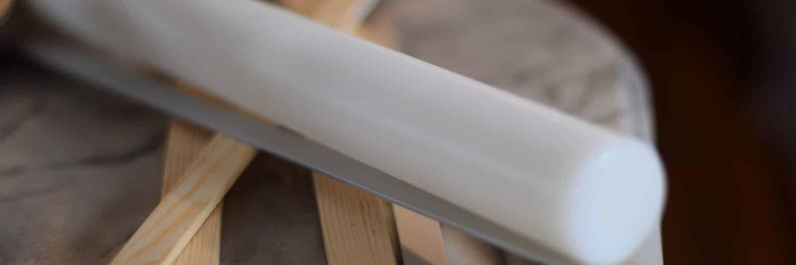 Glutenvrij. Witte deegroller met diverse uitrolstokjes van hout en metaal, als mikado stokjes op een marmeren blad.