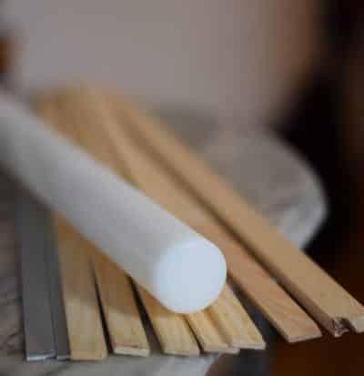 Witte plastic deegroller met diverse uitrolstokjes van hout en metaal