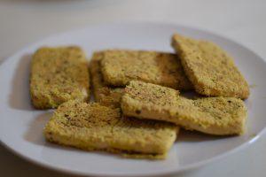 Glutenvrij eten. Schaal vol met tofoe, gepaneerd met polenta en provencaalse kruiden. Gebakken in olijfolie.