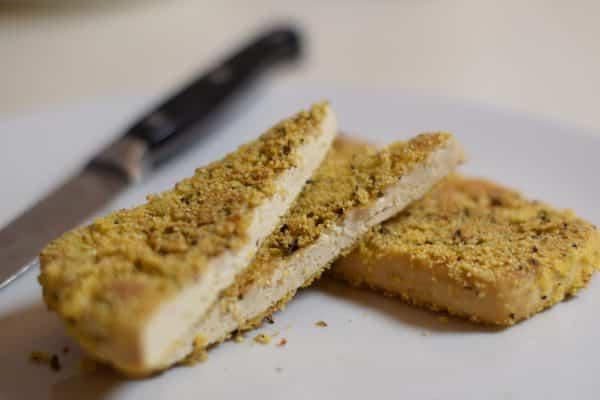 Vegan Met polenta en provencaalse kruiden gepaneerde tofoe, bruin en knapperig gebakken in olijfolie.