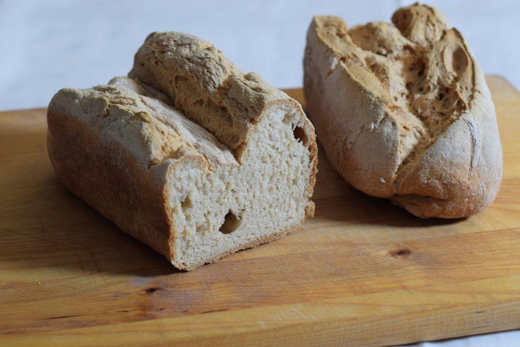 Glutenvrij, 2 mooi gerezen glutenvrije broden op een houten snijplank