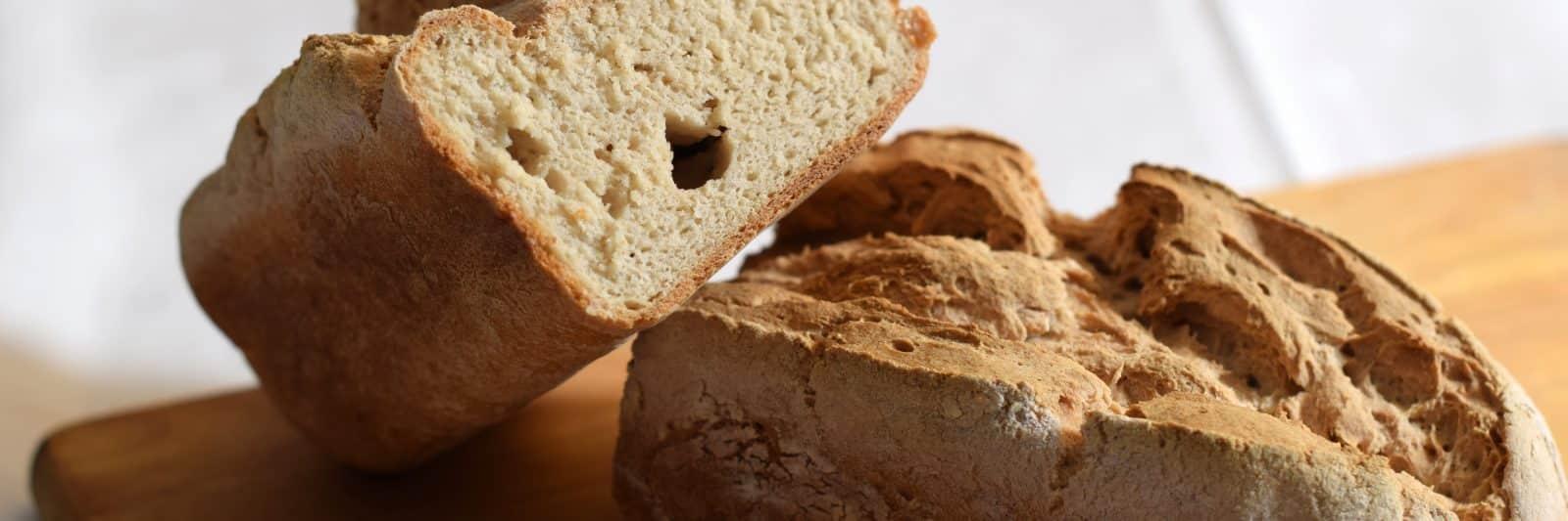 Glutenvrij brood bakken, 2 mooi gerezen glutenvrije broden opgestapeld op een houten snijplank
