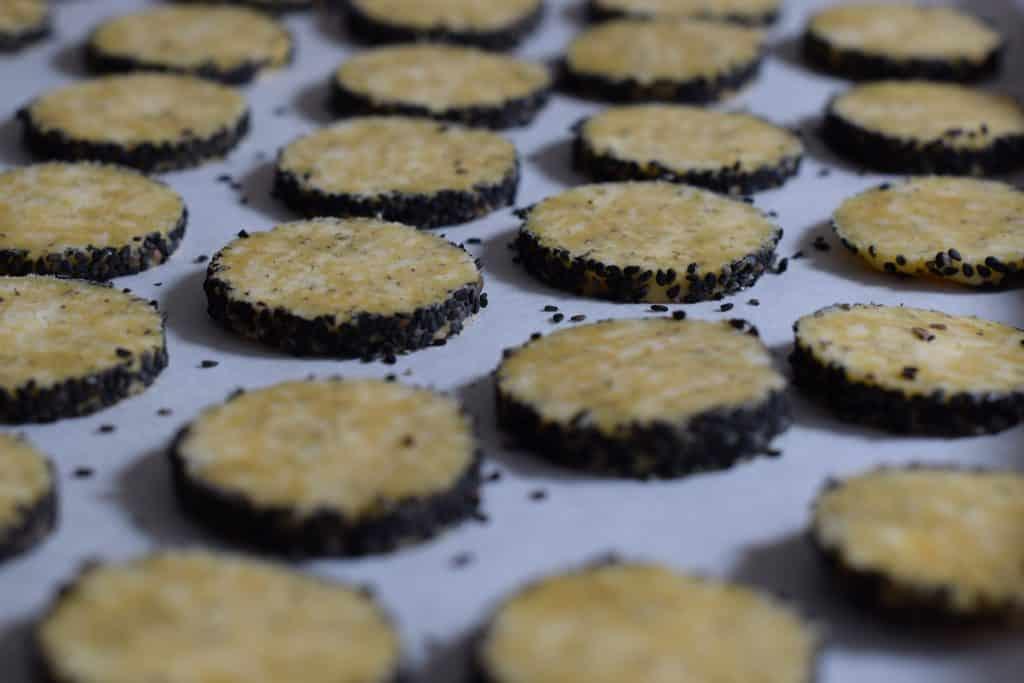 bakplaat vol ongebakken kaaskoekjes met een rand van nigella zaadjes (zwart sesamzaad)