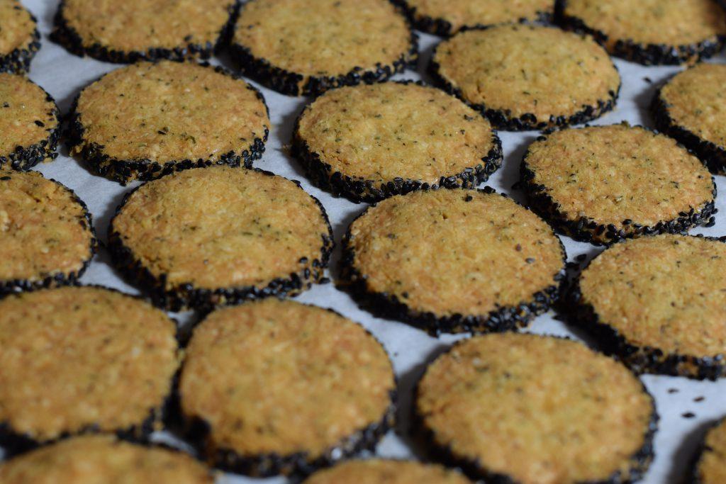 bakplaat vol bruin gebakken kaaskoekjes met een rand van nigella zaadjes (zwart sesamzaad)