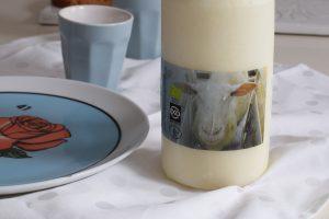 duurzaam eten. Fles met schapenmelk en blauwe beker en bord