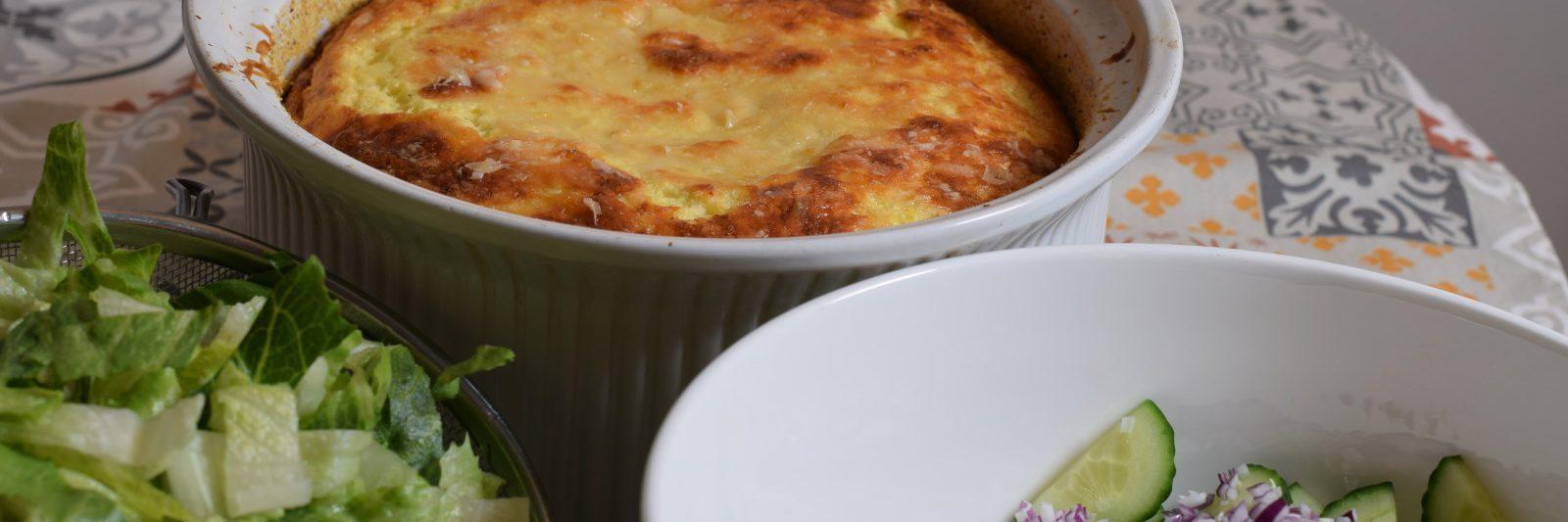 Bloemkool recept Bruin gebakken bloemkoolsoufflé in ronde ovenschaal, met sla, rode ui en komkommer op de voorgrond