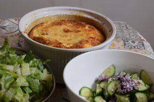 Bruin gebakken bloemkoolsoufflé in ronde ovenschaal, met sla, rode ui en komkommer op de voorgrond
