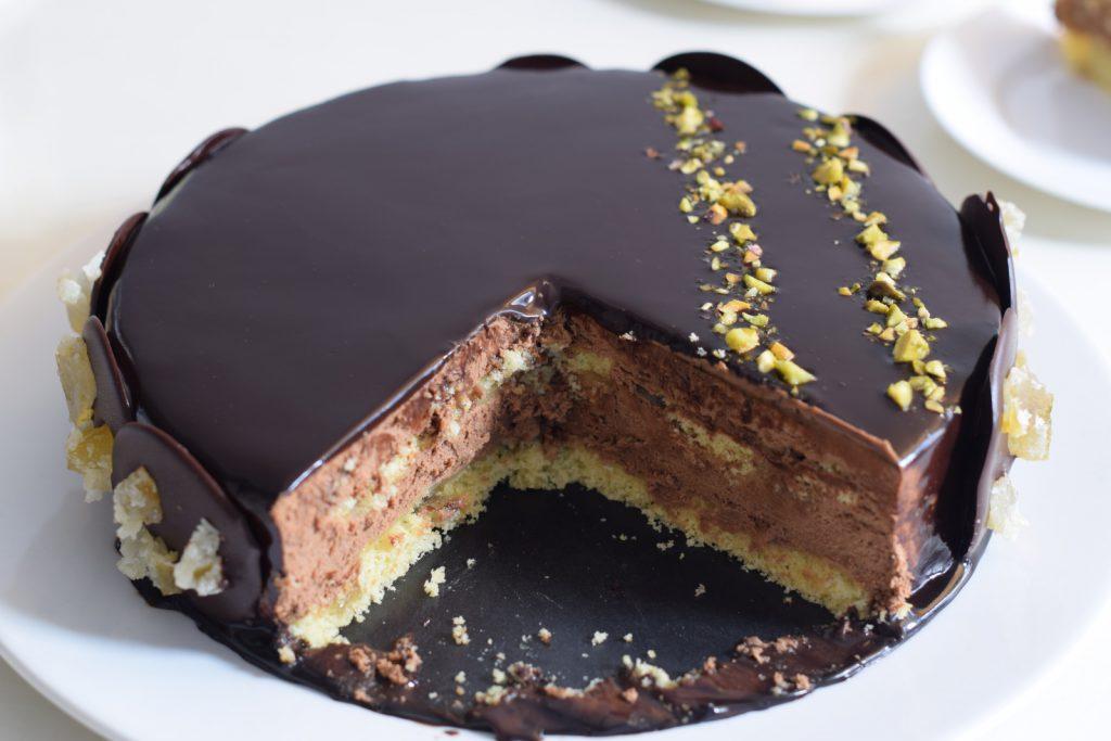 Glutenvrije patisserie, aangesneden chocoladekarameltaart met glimmende chocolade spliegel en galetjes met sukade