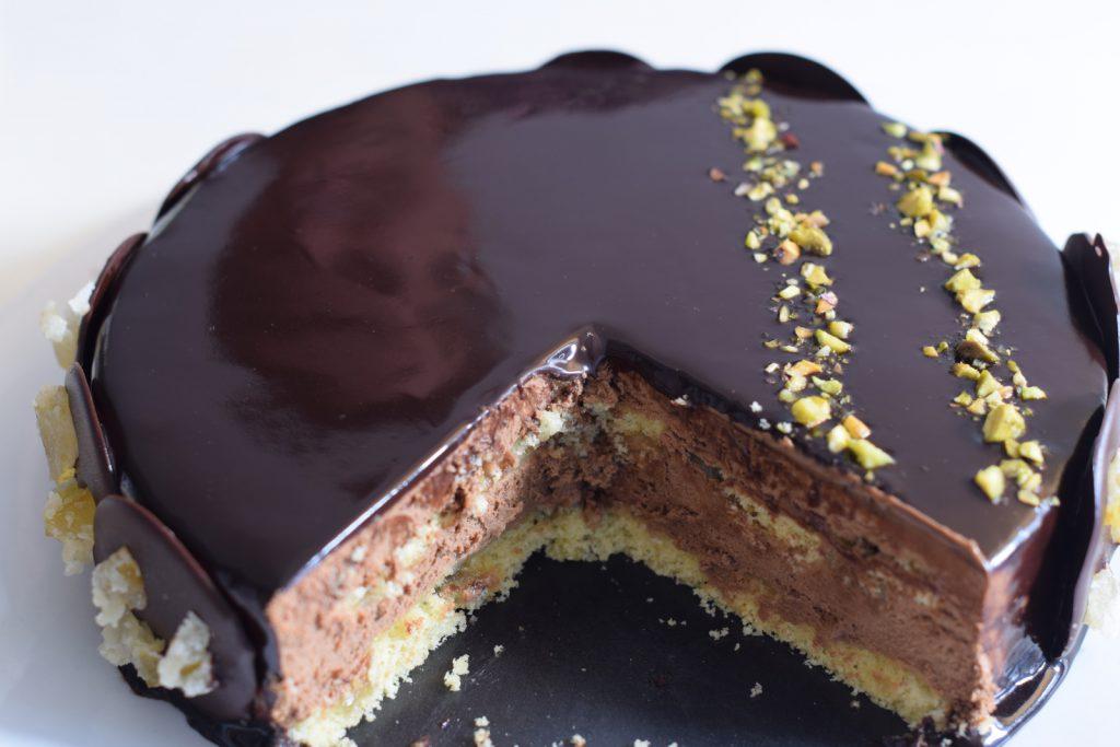 Glutenvrije chocolade taart, aangesneden chocoladekarameltaart met glimmende chocolade spliegel en galetjes met sukade, met weerspiegeling van een gezicht erop