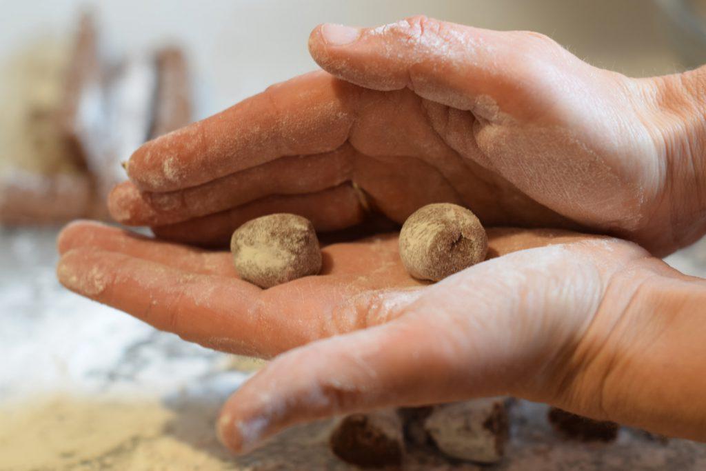 twee bolletjes chocolade truffel vulling, worden tussen twee handpalmen gerold