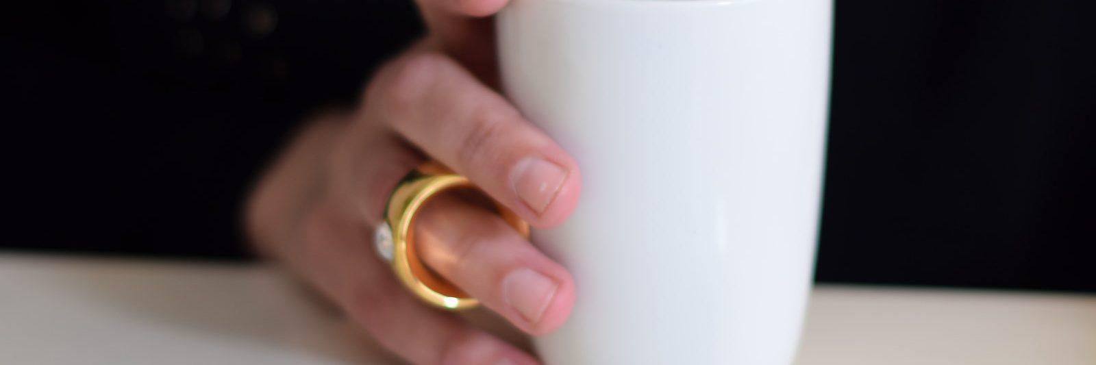 hand met witte koffiebeker met goudenring, waar een Marc de Champagne truffel voor ligt, op zwarte achtergrond