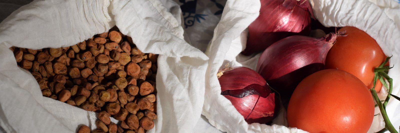 Duurzaam leven, stoffen zakjes, gevuld met grauwe erwten, rode uien en trostomaat.