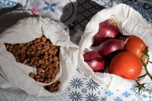 Duurzame stoffen zakjes, gevuld met grauwe erwten, rode uien en trostomaat.