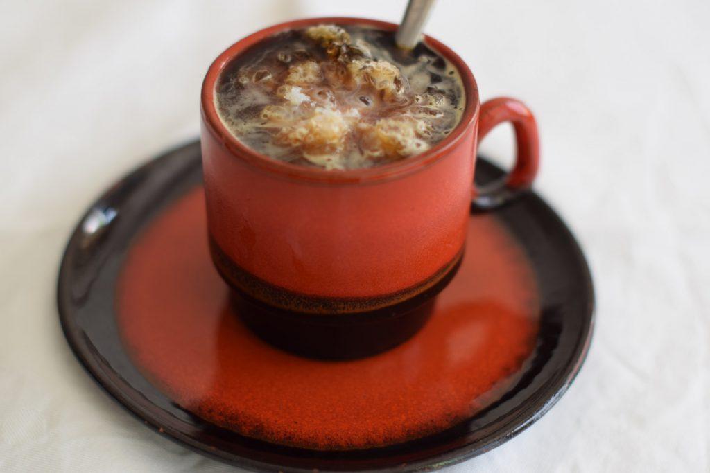 ijskoffie met een wolkje melk, in bruin/oranje jaren '70 stijl koffie kopje met schoteltje