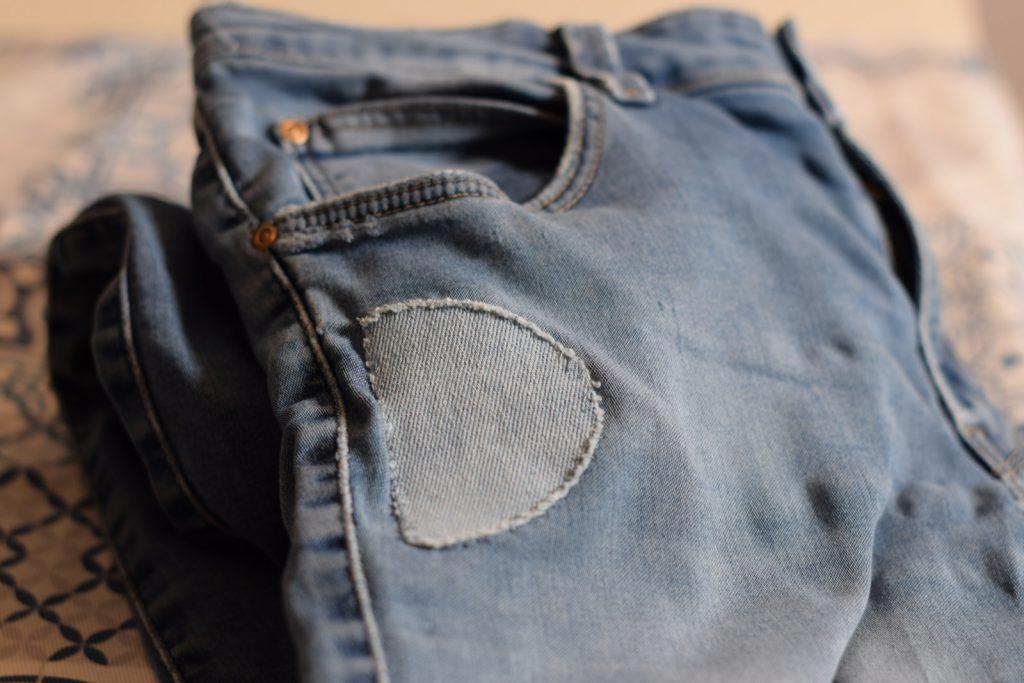 Spijkerbroek, opgelapt met opstrijkstuk in lichtere kleur.