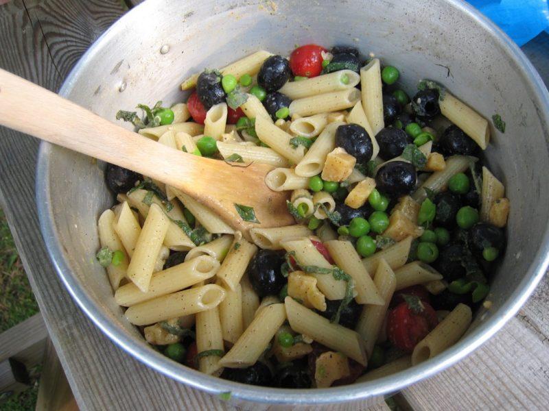 Koken op de camping. glutenvrije pasta met olijven, verse doperwtten en munt