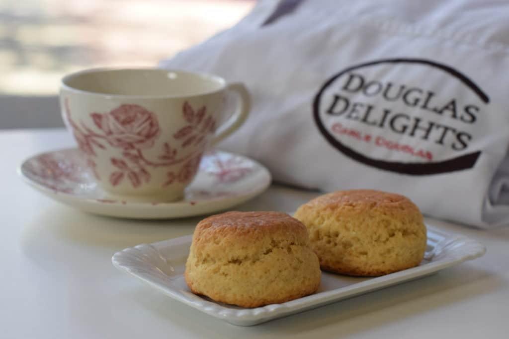 DouglasDelights, twee scones op een schoteltje met theeservies ernaast