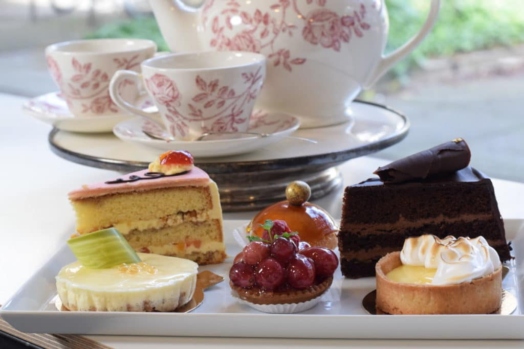 DouglasDelights, assortiment met taartjes op een plateau met daarachter theeservies