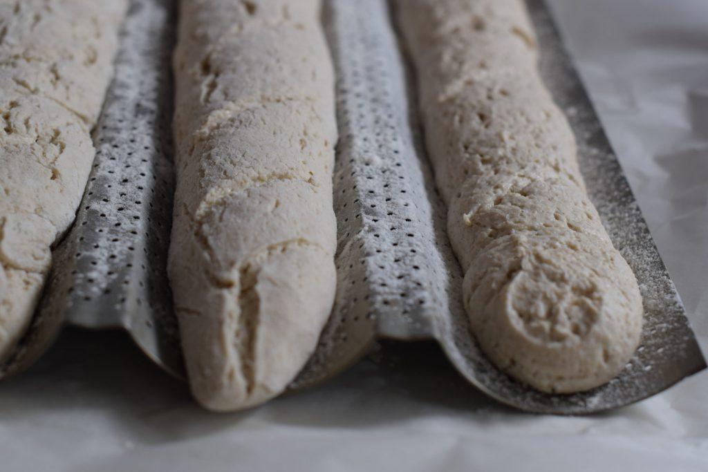 glutenvrij stokbrood met desem, drie gerezen stokbroden op een bakplaat met gaatjes
