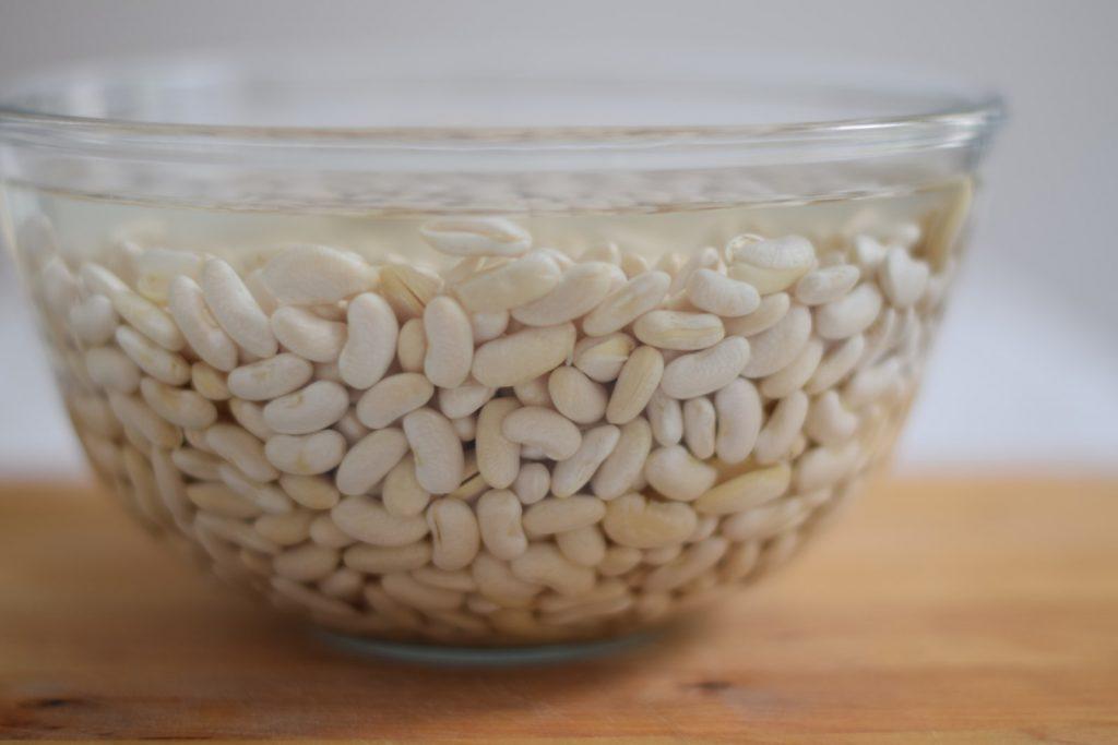 bonen koken, krombekbonen soep, glazen schaal met witte bonen in weekwater