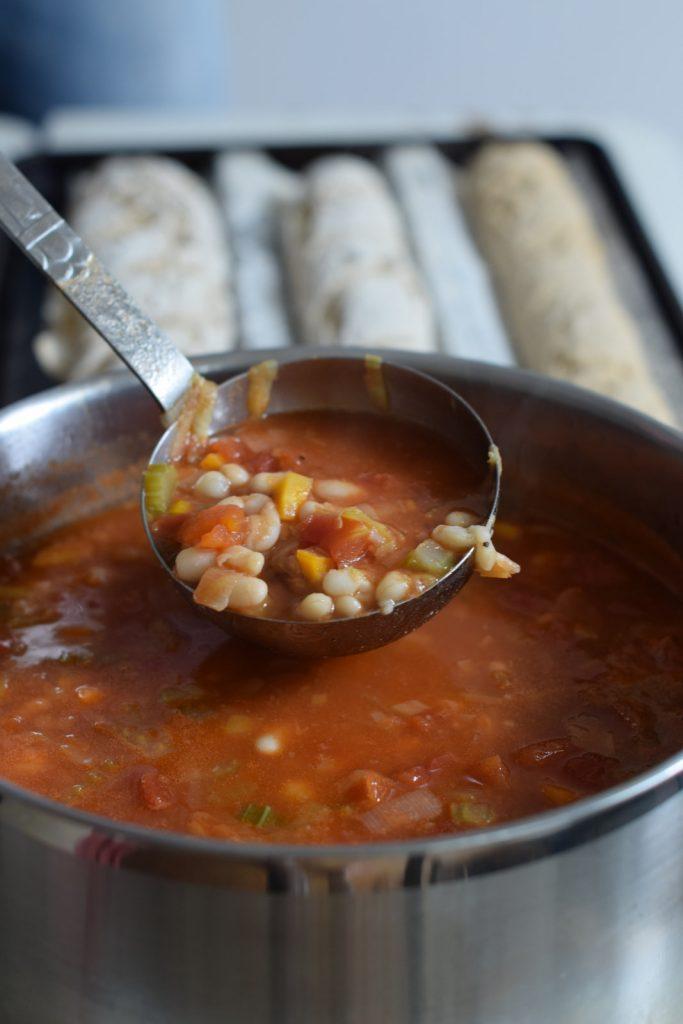 krombekbonen soep, grote pan vol met veel groentes en stokbroden op de achtergrond