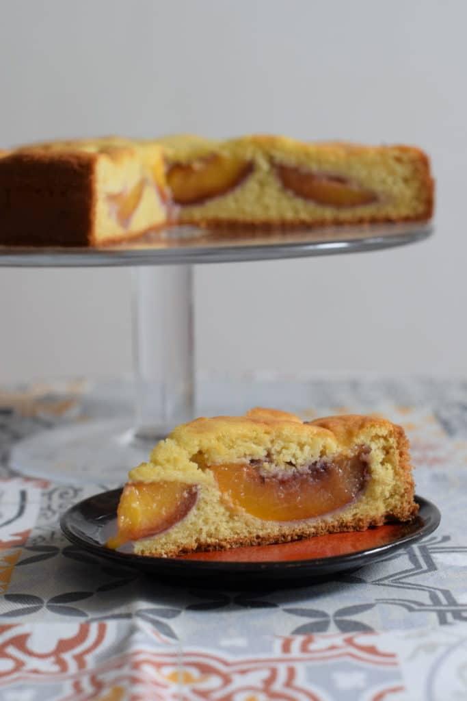 Glutenvrije oma's cake met nectarine, doorsnede van een cakepunt met daarachter de aangesneden cake op een glazen plateau
