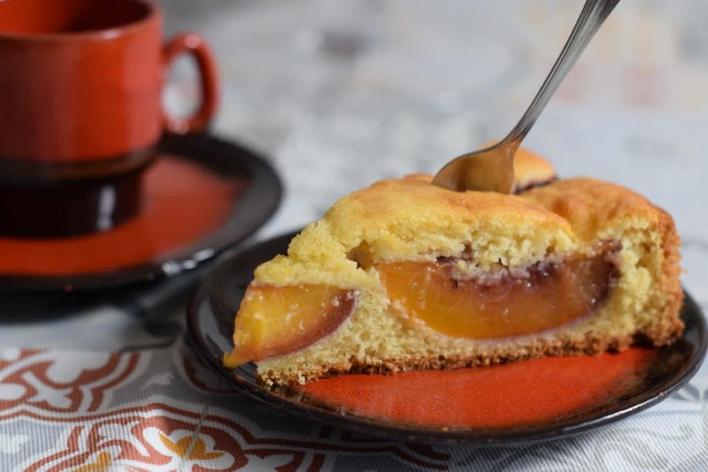 Glutenvrije oma's cake met nectarine, puntje cake met vork op een roodbruin schoteltje