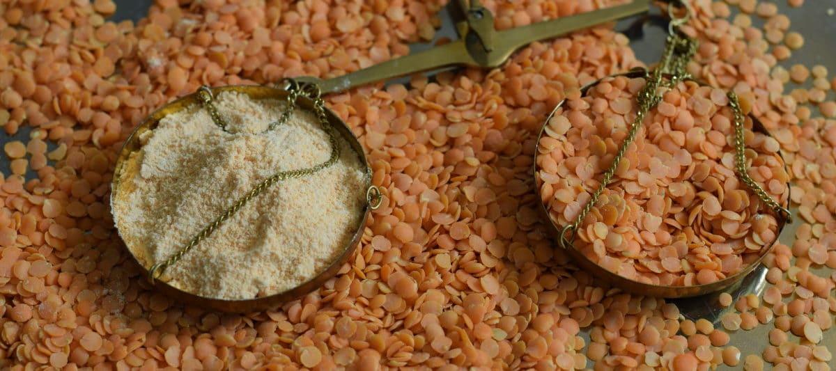 Zelf linzenmeel maken van rode linzen. Schaal met linzen en linzen meel op een koperen weegschaaltje
