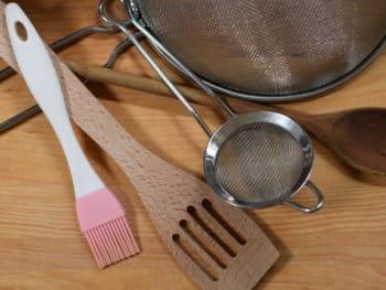 glutenvrije keuken, keukengereedschap op een houten plank. Twee zeven, houten pollepel en spatel en siliconen kwastje.
