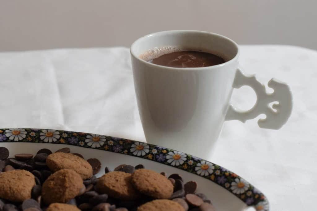 chocolademelk gemaakt met havermelk in een wit porseleinen kopje met een oor in de vorm van een strijkinstrumenten kam. Op de voorgrond een schaaltje kruidnoten en chocolade