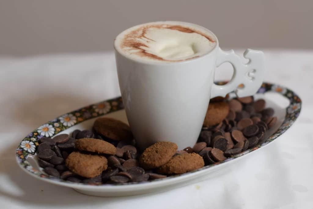 lekker eten en drinken, chocolademelk met slagroom in een wit porseleinen kopje met een oor in de vorm van een strijkinstrumenten kam. Kopje staat op een schaaltje met kruidnoten en chocolade