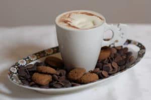 Warme chocolade melk met slagroom, op een ovaal schaaltje met bloemetjes, met pepernoten chocolade callets.