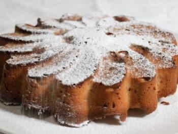 kersen cake in bloemvorm waar poedersuiker op wordt gestrooid