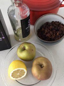 Mise en place voor mincemeat maken, rozijnen, goudreinetten, citroen en whiskey fles. Met een rode pan op de achtergrond.