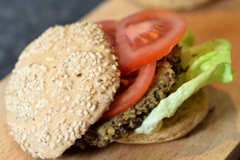 Vegetarische hamburger gemaakt met adukibonen. Geserveerd met sla, plakjes tomaat en een glutenvrij hamburgerbroodje.