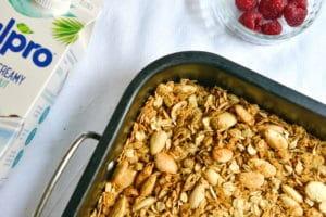 Zelf granola maken, bakplaat vol granola met een bakje frambozen ernaast