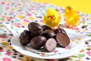 Lindt Lindor zelfgemaakte chocolade paaseitjes op een schoteltje met 2 gele paaskuikentjes en een kleurig bloemig kleed en servet