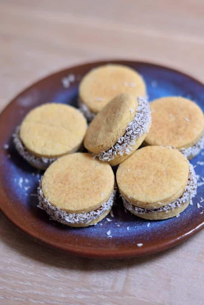 Glutenvrije alfajores, Argentijnse koekjes naar het lievelings recept van Maxima. Zes dubbele koekjes gedecoreerd met kokos, op een bruin blauw bordje.