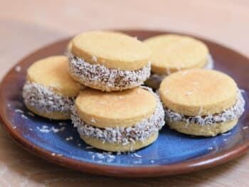Alfajores glutenvrij, stapel dubbele koekjes gedecoreerd met geraspte kokos.