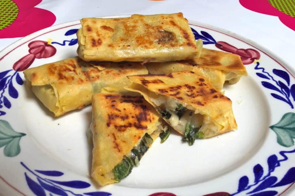 Loempiaatjes van kikkererwtenmeel filodeeg, mooi bruin gebakken en opgestapeld op een boerenbonte bord