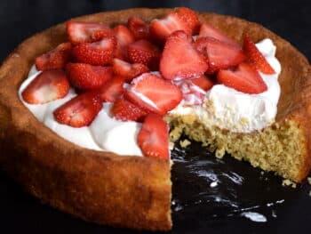 aardbeientaart recept. aangesneden taartin laagjes, cakebodem met daarop slagroom en heel veel gehalveerde aardbeien.