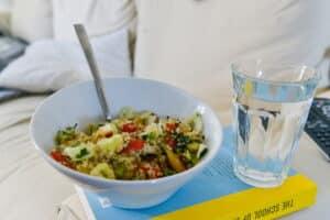 quinoa salade met gebakken halloumi in een witte kom met een groot glas water ernaast