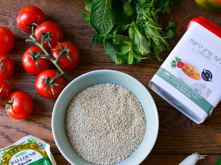 quinoa salade mise en place met verse groene kruiden, fel rode tomaten, een pakje halloumi en bouillon