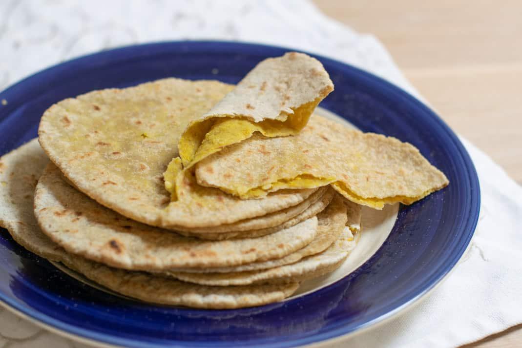 Roti vellen maken met glutenvrij meel en chana dal vulling. stapel roti's met bovenop een open gescheurde roti met fel gele chana dal vulling