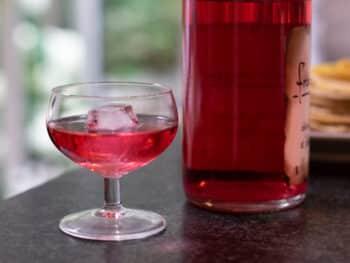 Eau de vie frambozen, mooi roze gekleurd in een glaasje met een ijsklontje. En de roze fles op de achtergrond.