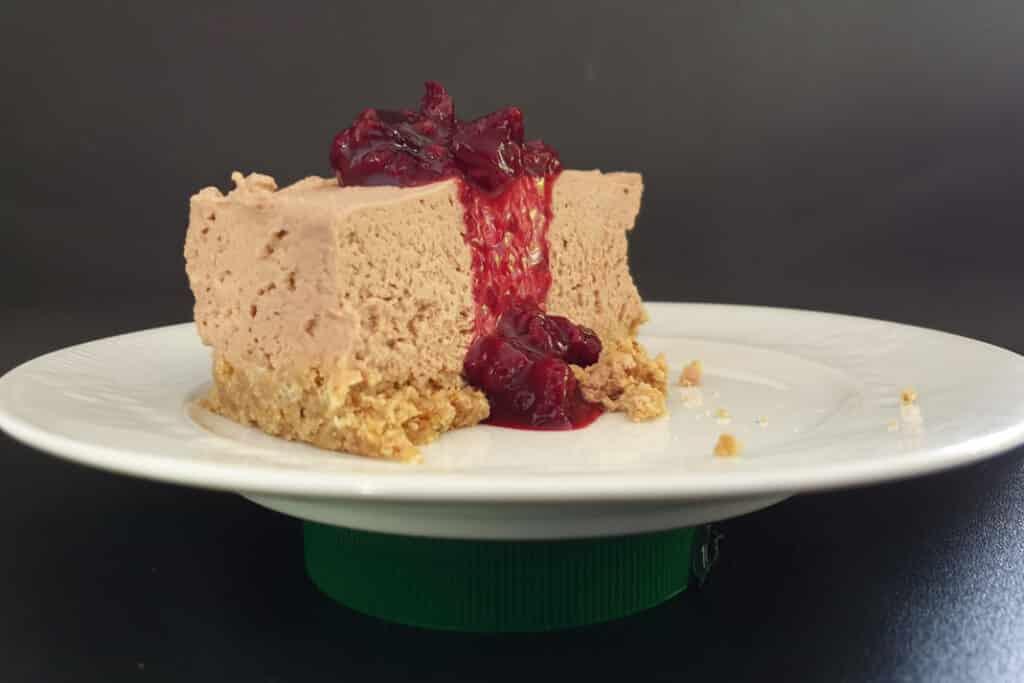 puntje no-bake melkchocolade cheesecake met daar boven op een grote schep frambozen topping