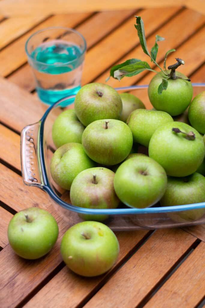 Appels, seizoensfruit, schaal vol appels met bladgroen er nog aan