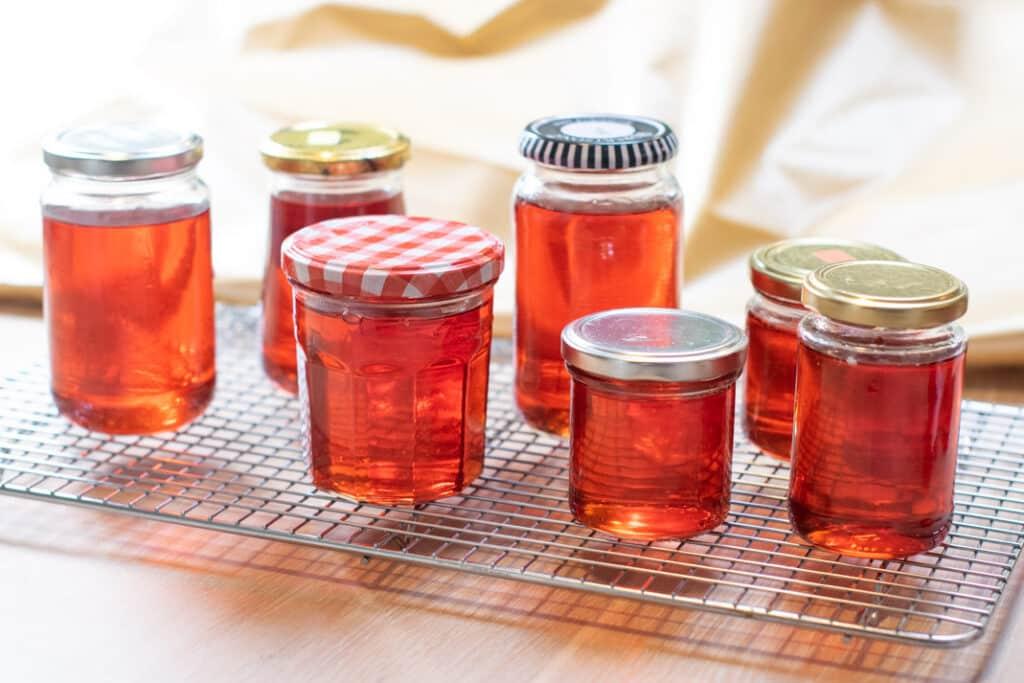 Kweepeer gelei in glazen potten, met een mooie heldere dieprode kleur en fraaie lichtinval.