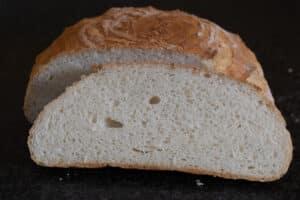 Aangesneden rond glutenvrij wit brood, gebakken in een pan